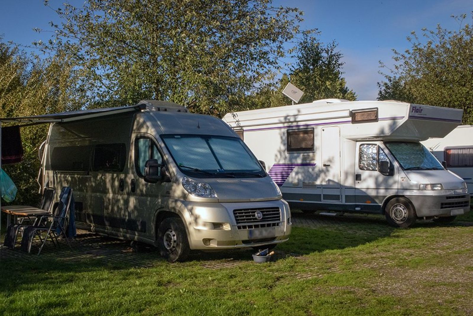 Two motorhome/camper pitches side by side on a corner